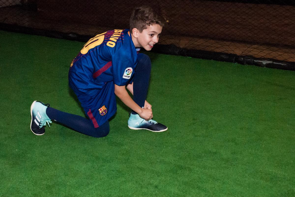 amarrando as chuteiras no Buffet Planeta Kids, aniversário de Gustavo 10 anos, tema da festa Barcelona