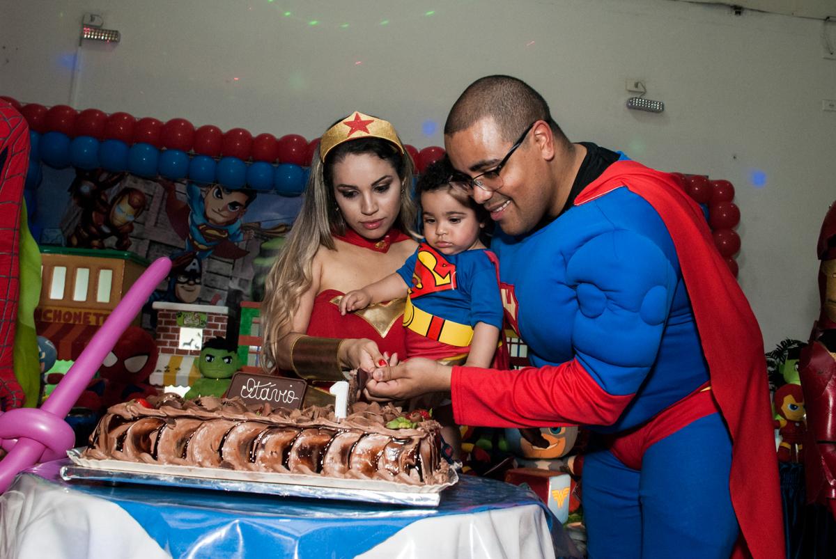 cortando o primeiro pedaço de bolo no buffet Zezé e Lelé, aniversário de Otávio 1 ano, tema da festa heróis baby