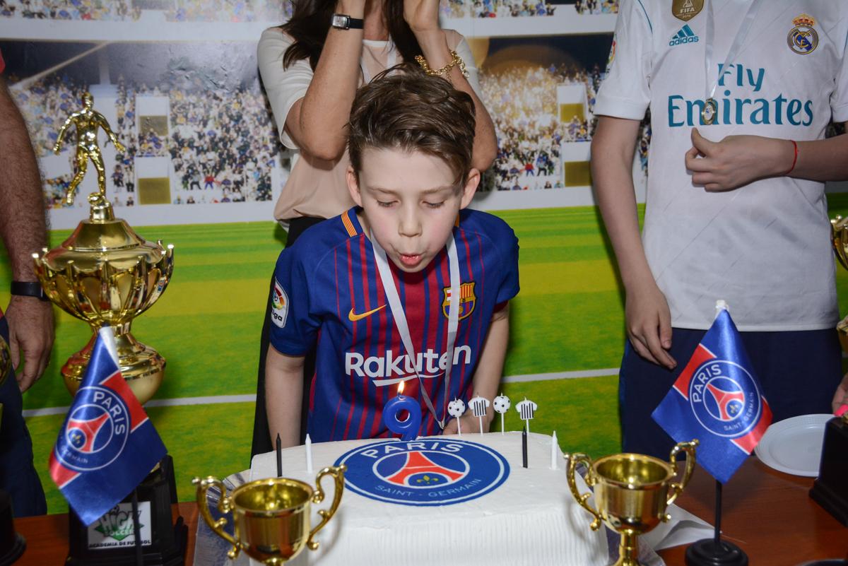 soprando a vela do bolo no Buffet High Soccer, aniversário de Daniel 9 anos, tema da festa futebol, time Barcelona