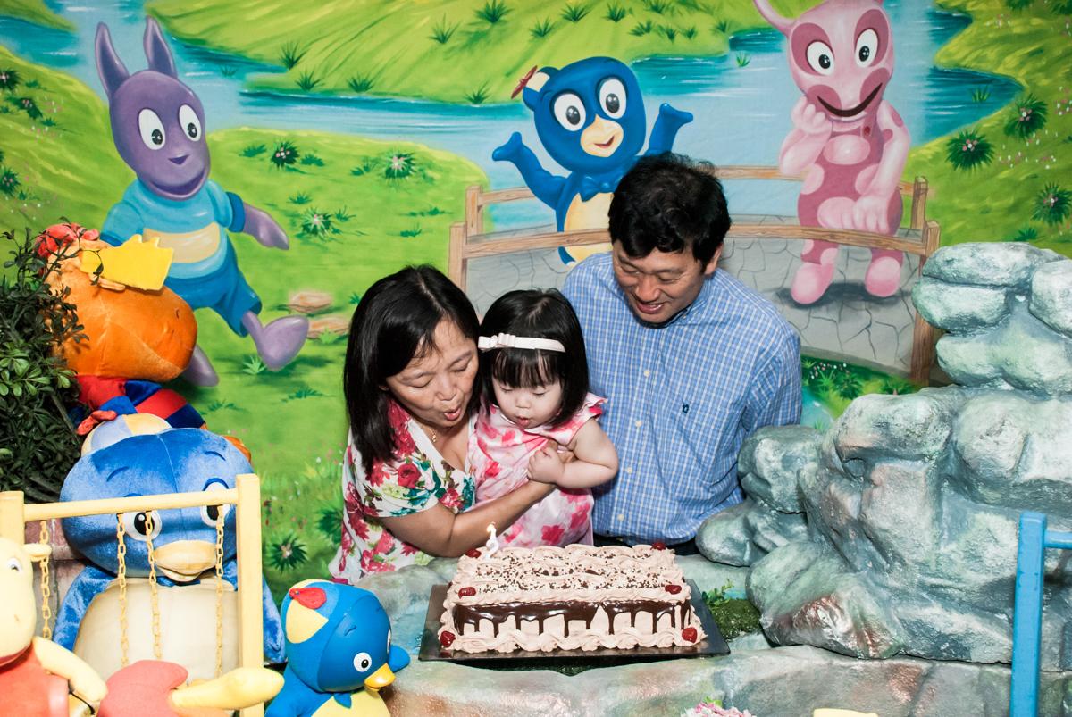 soprando a vela do bolo no fotografia da família na mesa temática no Buffet Viva Vida, Butantã, São Paulo, aniversário de Julia Yumi, tema da festa Backardigans