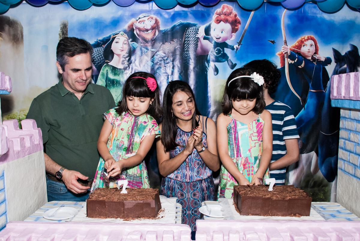 cortando o primeiro pedaço de bolo no Buffet Magic Joy, Saúde, São Paulo, aniversário de Beatriz e Marina, tema da festa Valente