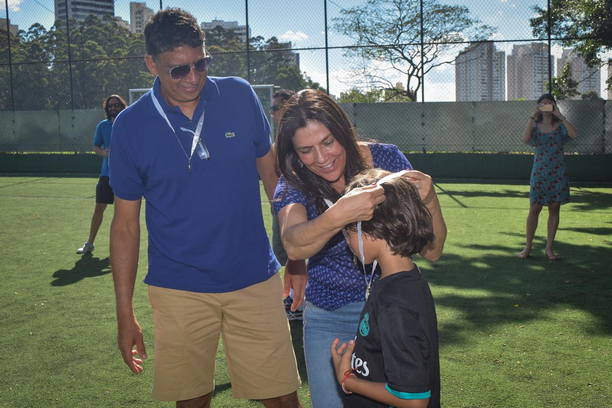 a mãe coloca a medalha no aniversariante no buffet High Soccer aniversario de João Pedro 8 anos, tema da festa Real Madrid