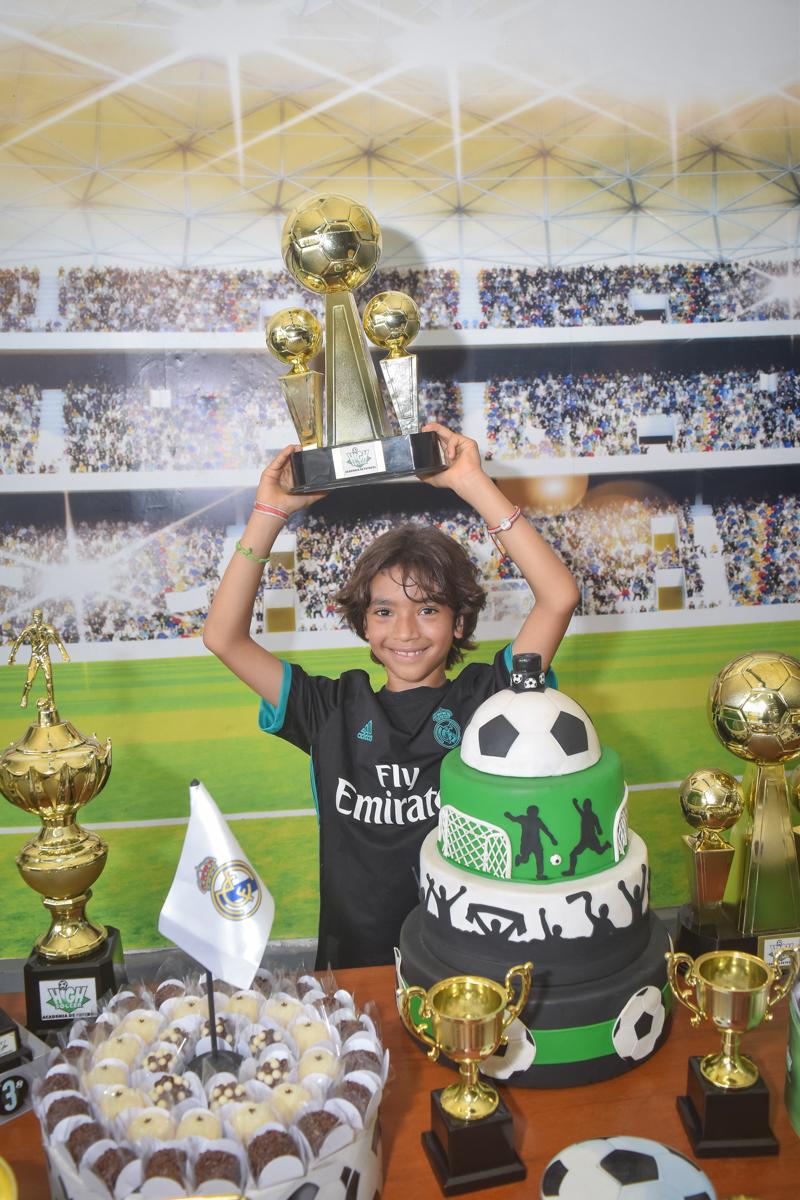 erguendo a taça no buffet High Soccer aniversario de João Pedro 8 anos, tema da festa Real Madrid