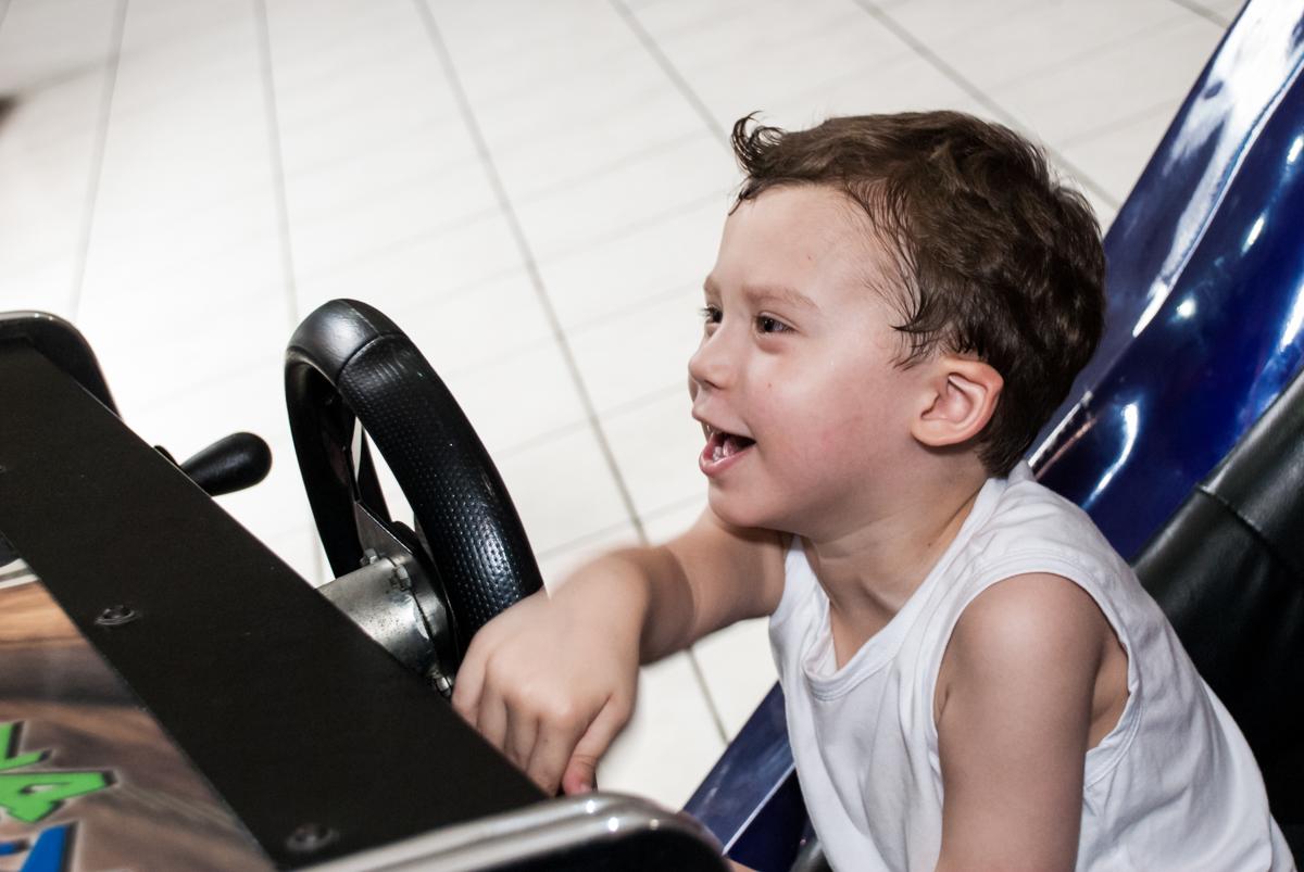 brincando com o simulador de corridas no Buffet Fábrica da Alegria, Osasco, aniversário de Arthur 4 anos, tema da festa Patrulha Canina