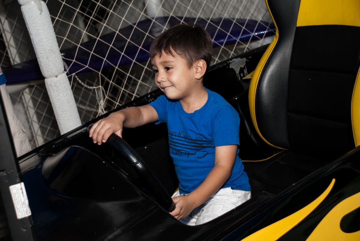 O amigo brinca no simulador de corrida no Buffet Fábrica da Alegria Morumbi, São Paulo, aniversário de João Pedro 4 anos tema da festa Batman