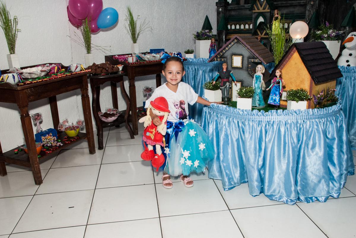 aniversariante faz foto em frente a mesa decorada no Buffet Fábrica da Alegria Morumbi, anieversário de Ana Julia 3 anos, tema da festa Frozen