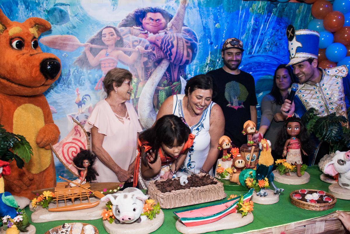 soprando a vela do bolo no Buffet Casa X, Ipiranga,São Paulo, aniversário de Raquel 6 anos, tema da festa Moana