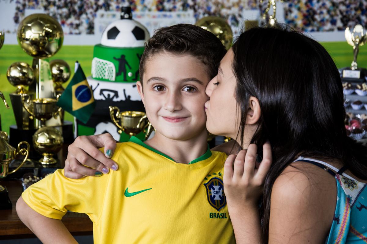 O aniversariante ganha beijo da irmã