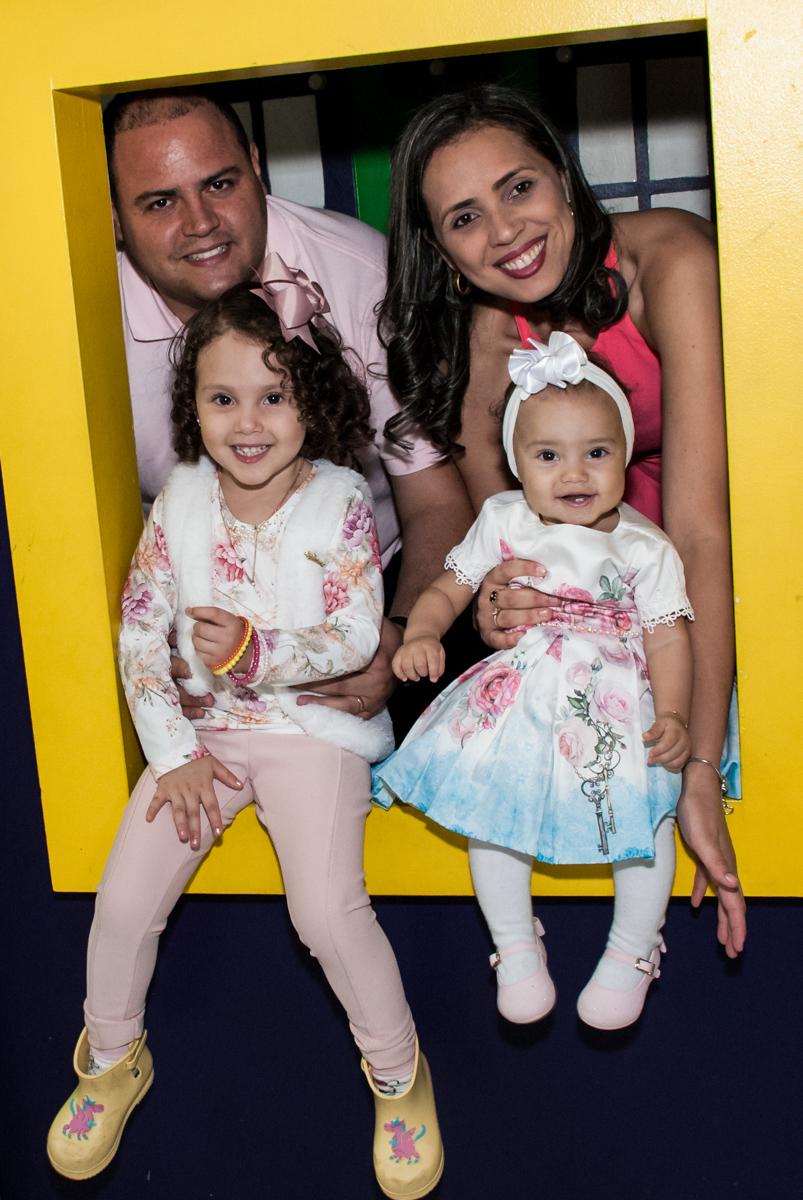 a família posam para a foto na janela da casa de bonecas