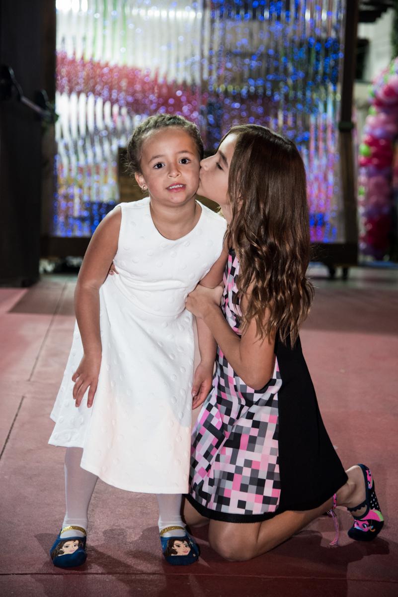 aniversariante sendo cumprimentada pela irma com beijinhos