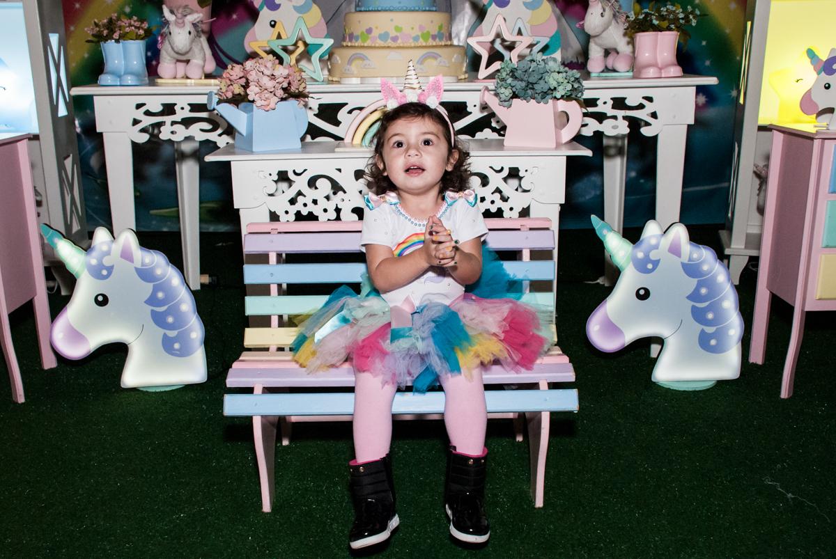 posando para a foto em frente a mesa temática unicornio