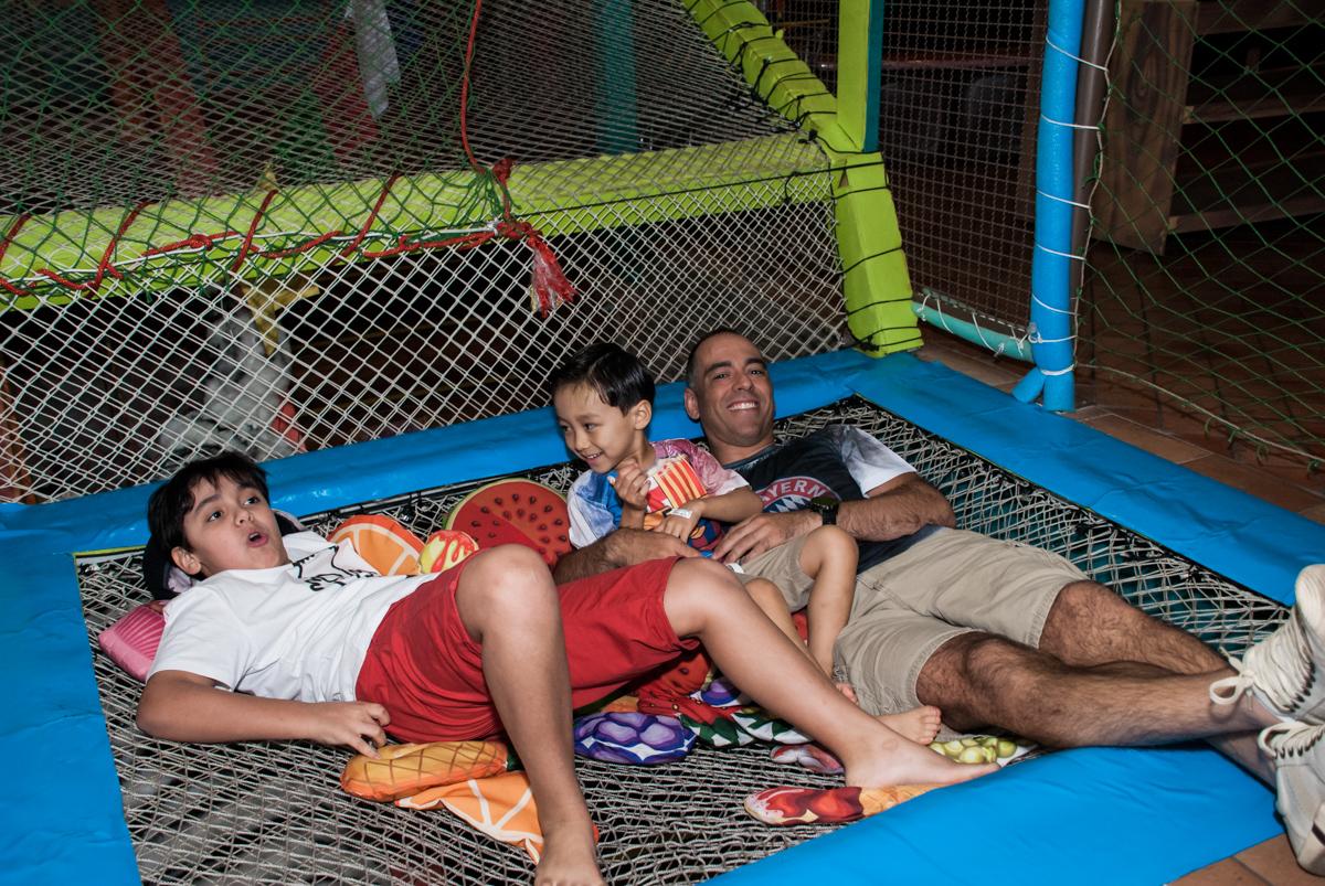 As crianças e o pai dos aniversariantes brincam na cama elastica