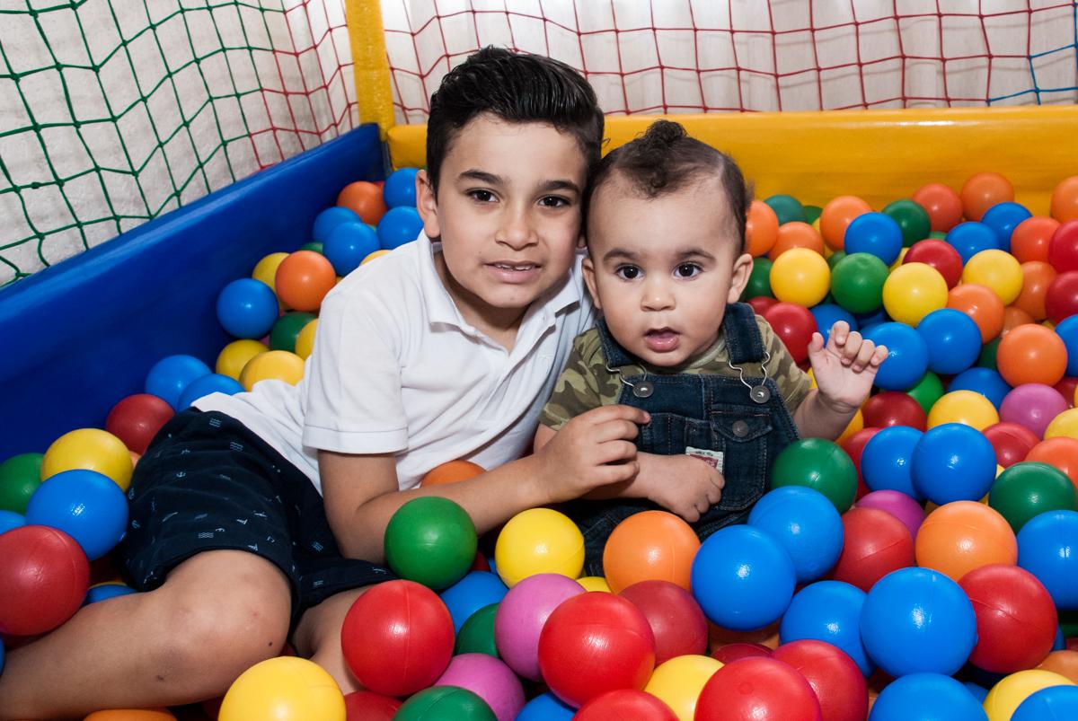 irmão e filho brincam na piscina de bolinhas