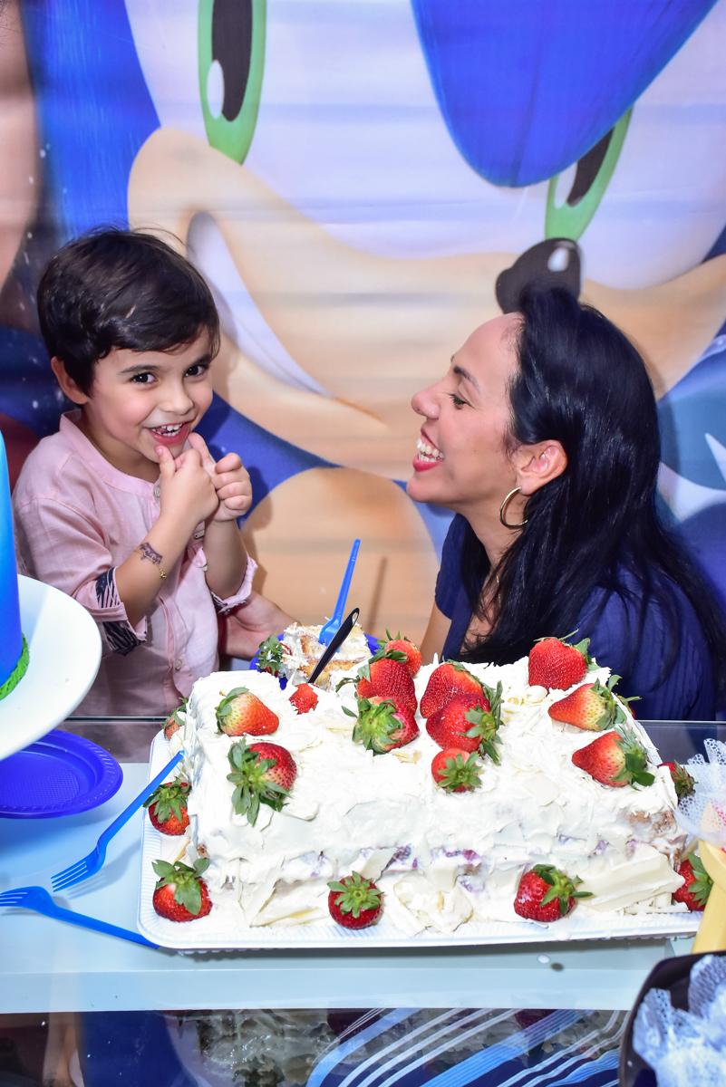 mãe feliz em receber o primeiro pedaço do bolo
