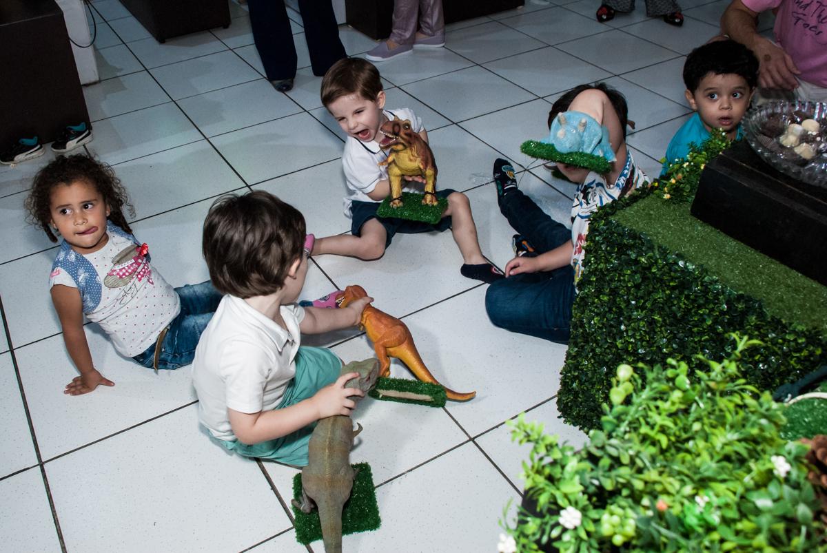 As crianças brincam com os dinossauros da mesa