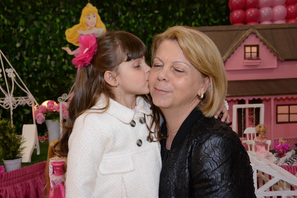 Fotografia da aniversariante beijando a vó em frente a mesa decorada Buffet Comics São Paulo SP