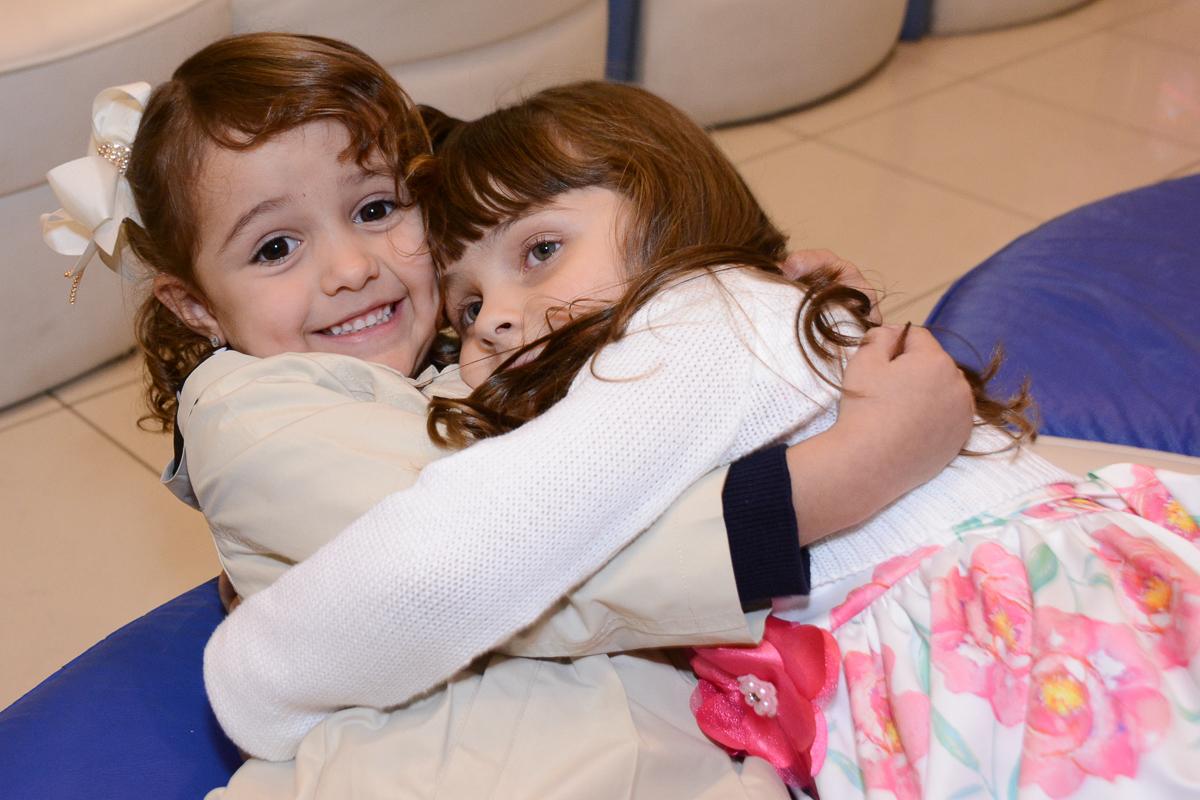 Fotografia da aniversariante abraçando amiguinha Buffet Comics São Paulo SP
