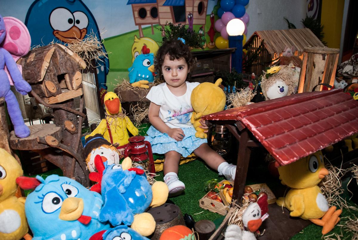 posando na mesa para a foto junto com os personagens da galinha pintadinha