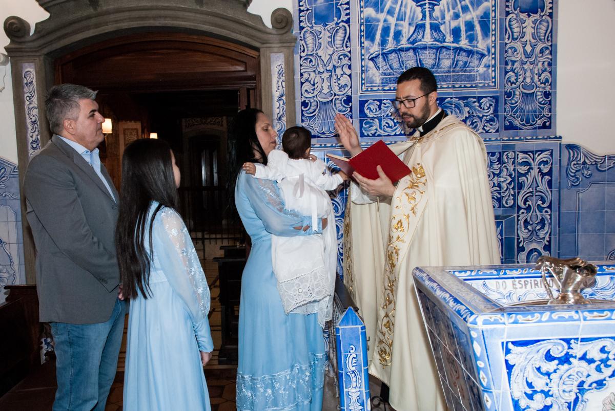 O padre faz o batizado