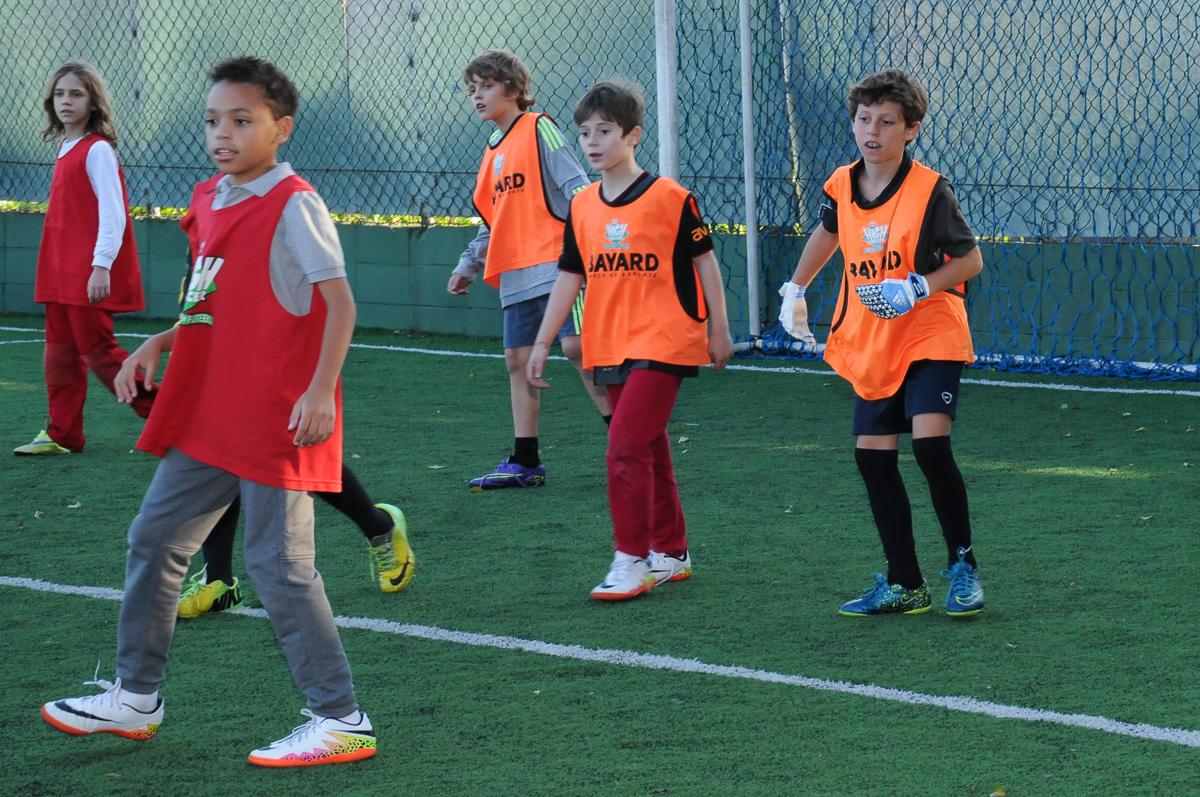 Fotografia de amigos jogando no campo de futebol do campo de futebol do High Soccer
