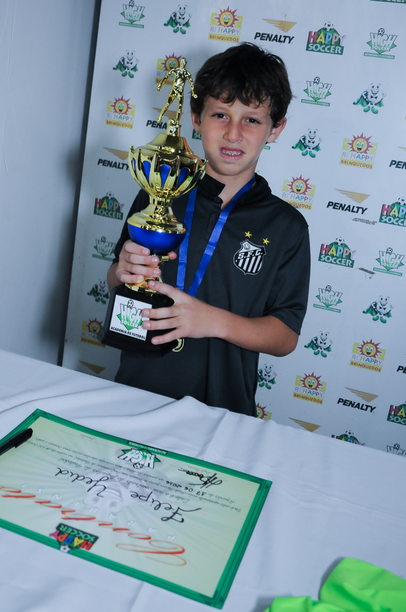 Fotografia do aniversariante com o troféu no Buffet High Soccer