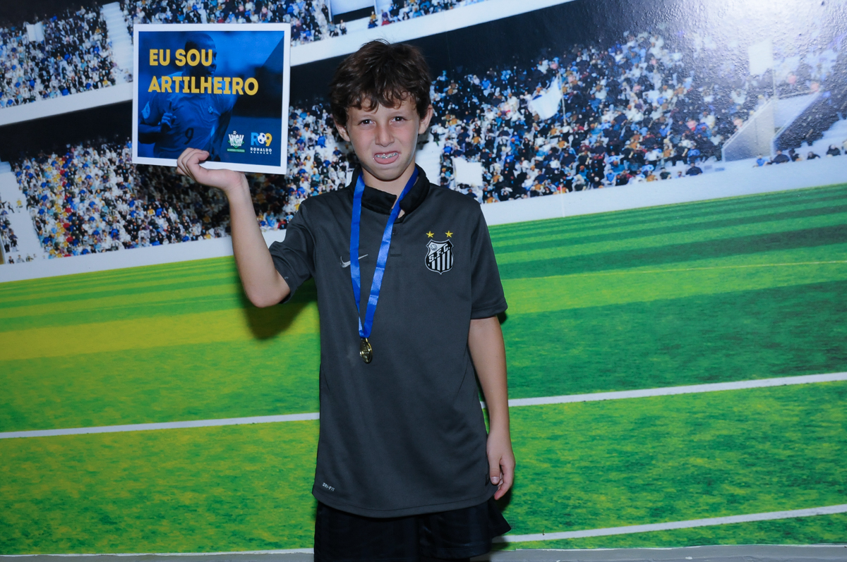 Fotografia do aniversariante no campo de futebol com a medalha no Buffet High Soccer
