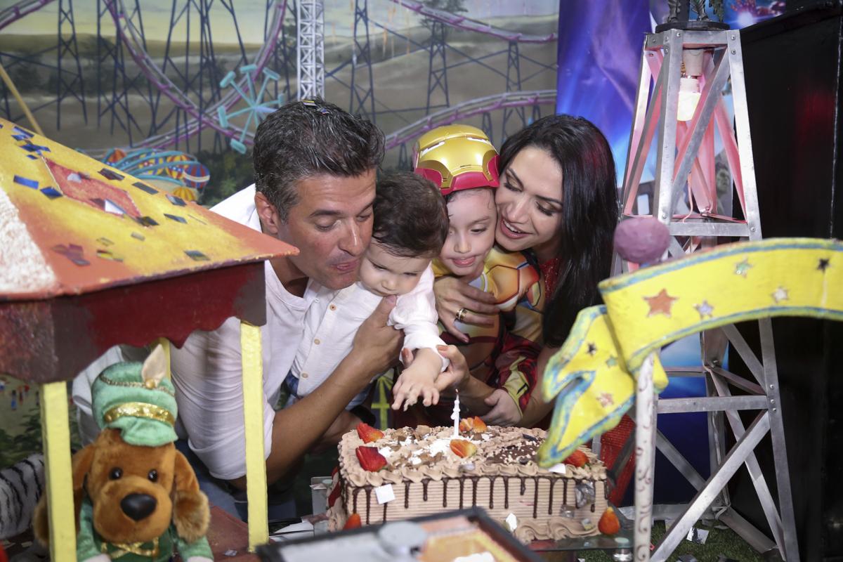 A família juntas sopram a vela do bolo