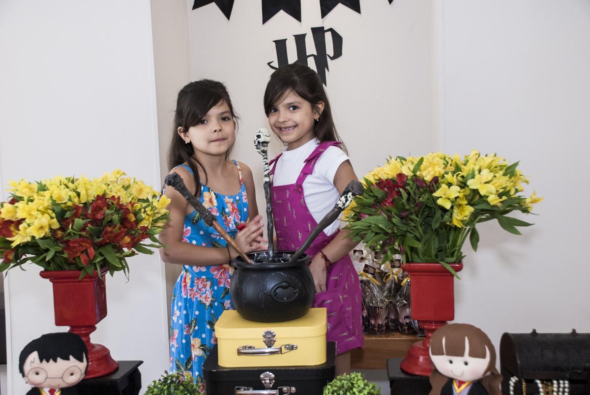 As gêmeas posasm para a foto no caldeirão