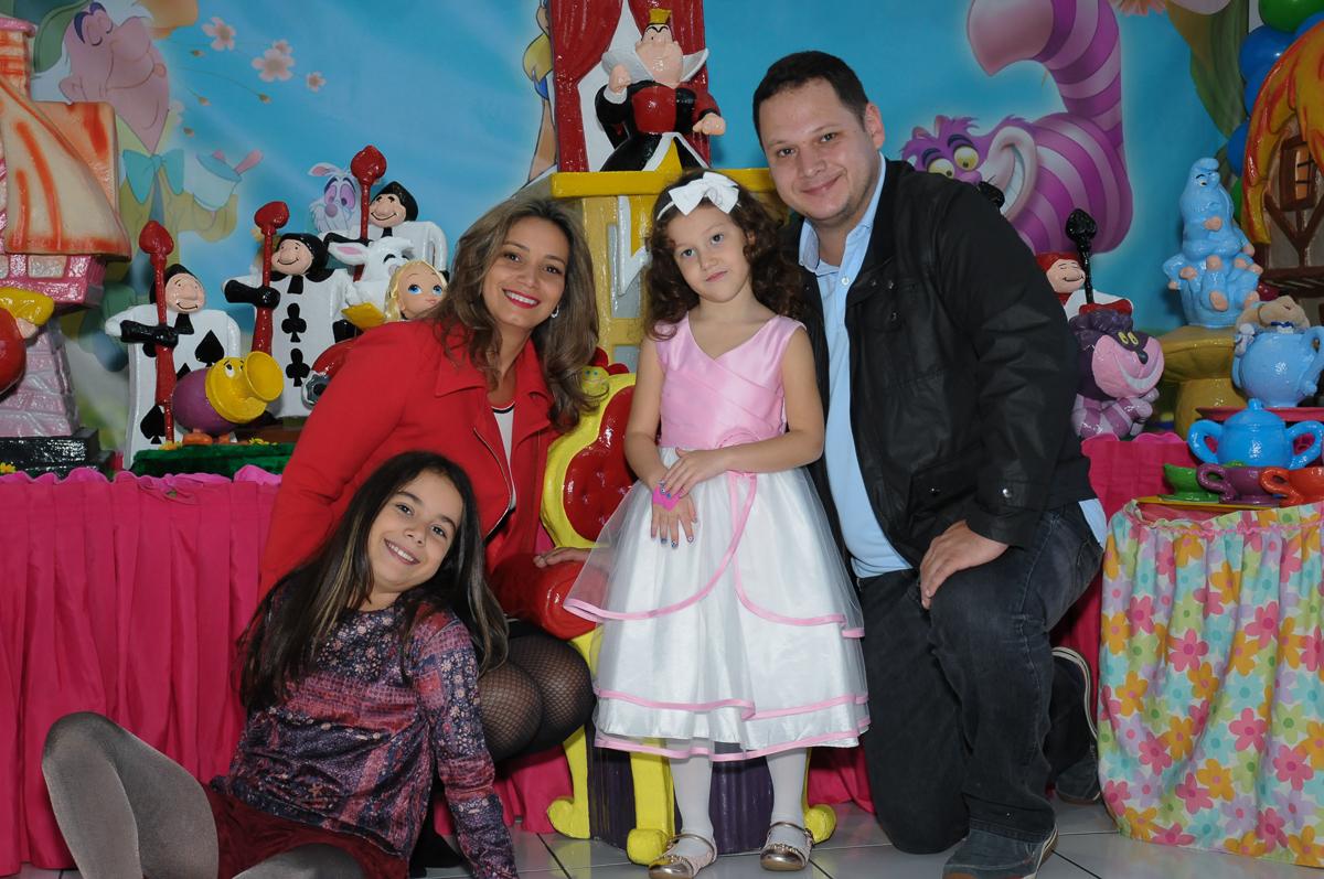 Fota da aniversariante dom os pais na mesa Alice no País das Maravilhas no Buffet Magic Joy