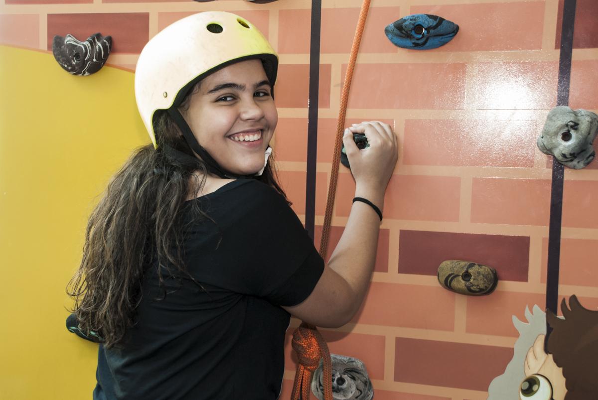 subindo a parede de escalada com um sorrisão