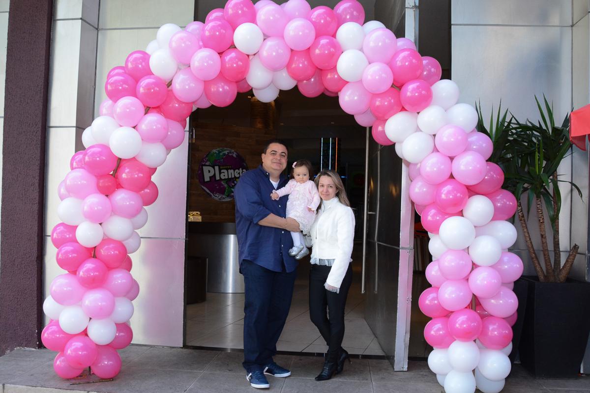 Lorena com papai e mamãe no arco de bexigas no Buffet Planeta Kids, São Paulo - SP
