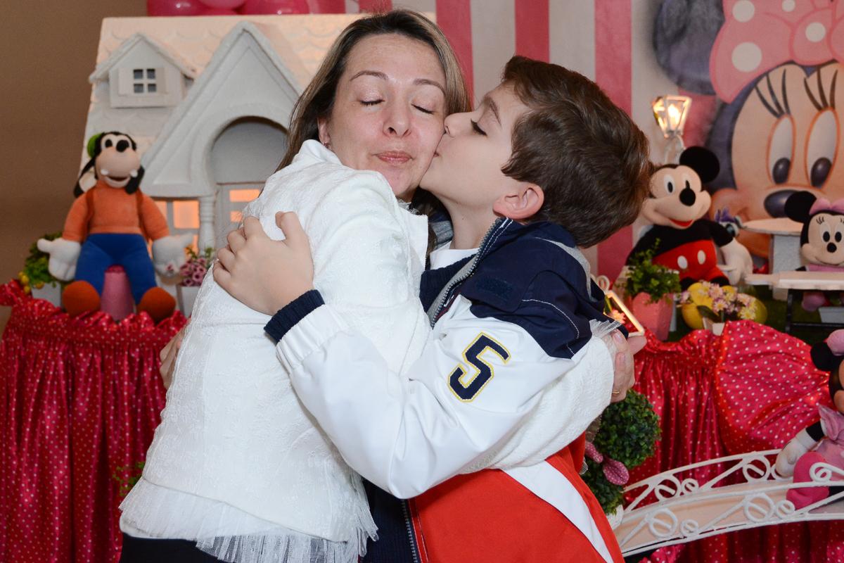 Irmãozinho de Lorena beijando a mamãe em frente a mesa decorada  no Buffet Planeta Kids, São Paulo - SP