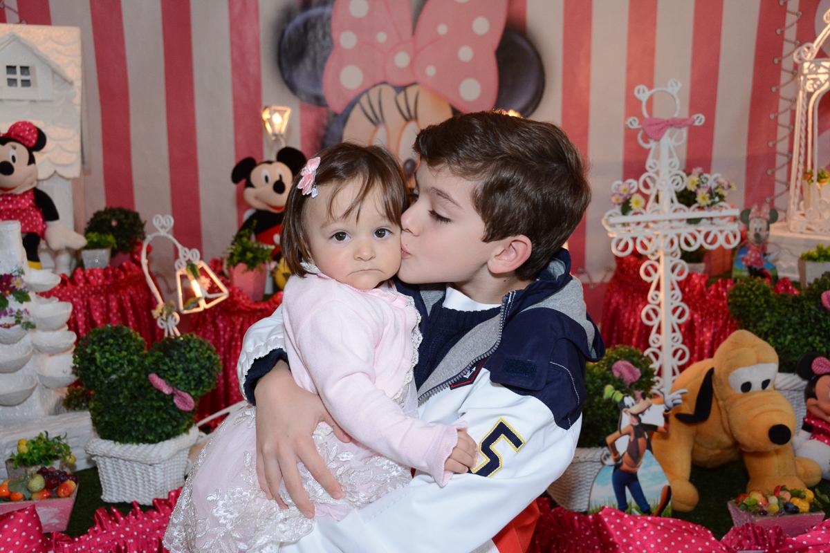 Irmão de Lorena a beija em  frente a mesa decorada   no Buffet Planeta Kids, São Paulo - SP