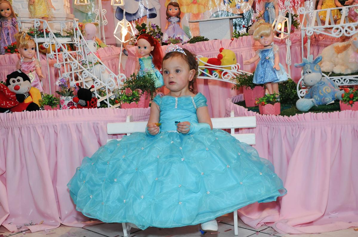 valentina vestida de princesa em frente a mesa do parabéns