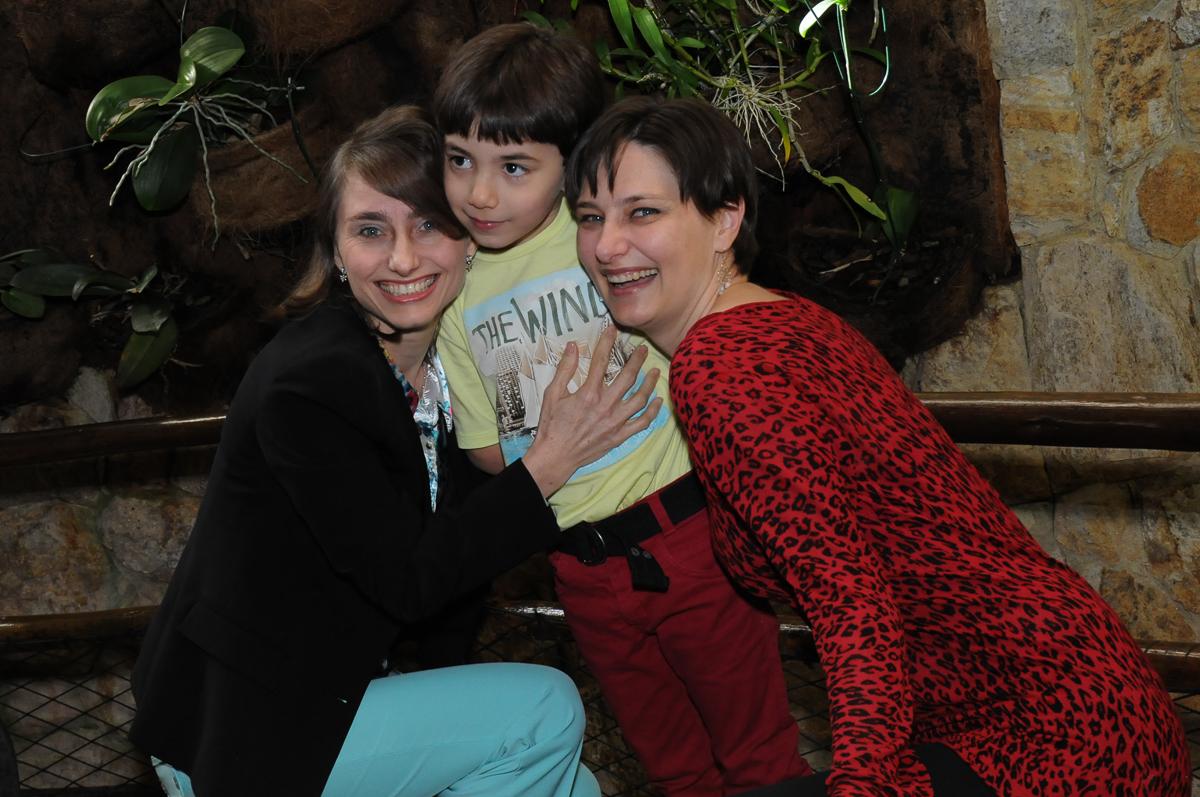 breno com a mãe e tia em frente a mesa decorada tema safari no Buffet Saphari - Campo Belo