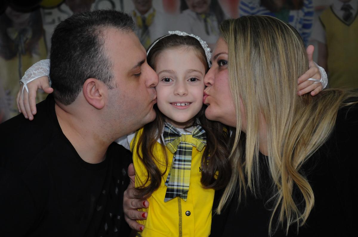 Lara ganhando beijinho dos pais no Buffet Zezé e Lelé