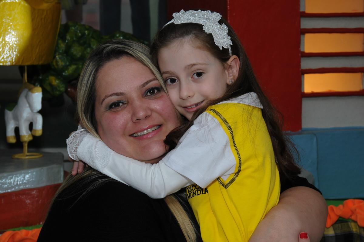 Lara com a mamãe em frente a mesa decorada carrossel no Buffet Zezé e Lelé