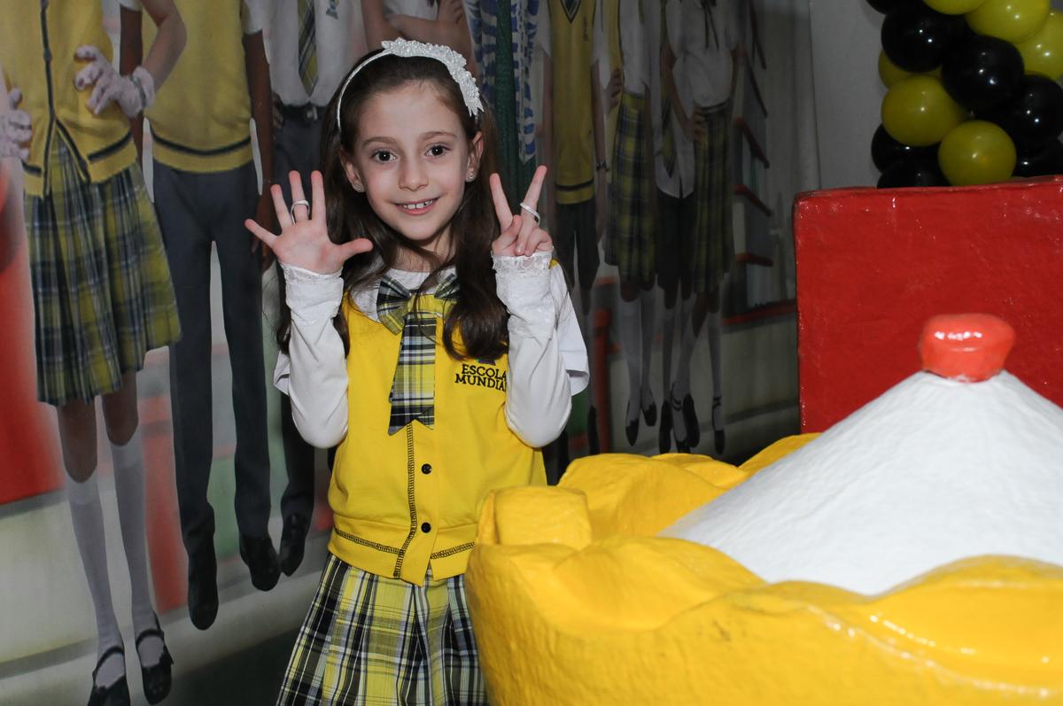 Lara em frente a mesa decorada carrossel no Buffet Zezé e Lelé