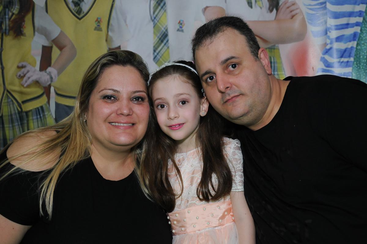 Lara com os pais em frente a mesa do bolo no Buffet Zezé e Lelé