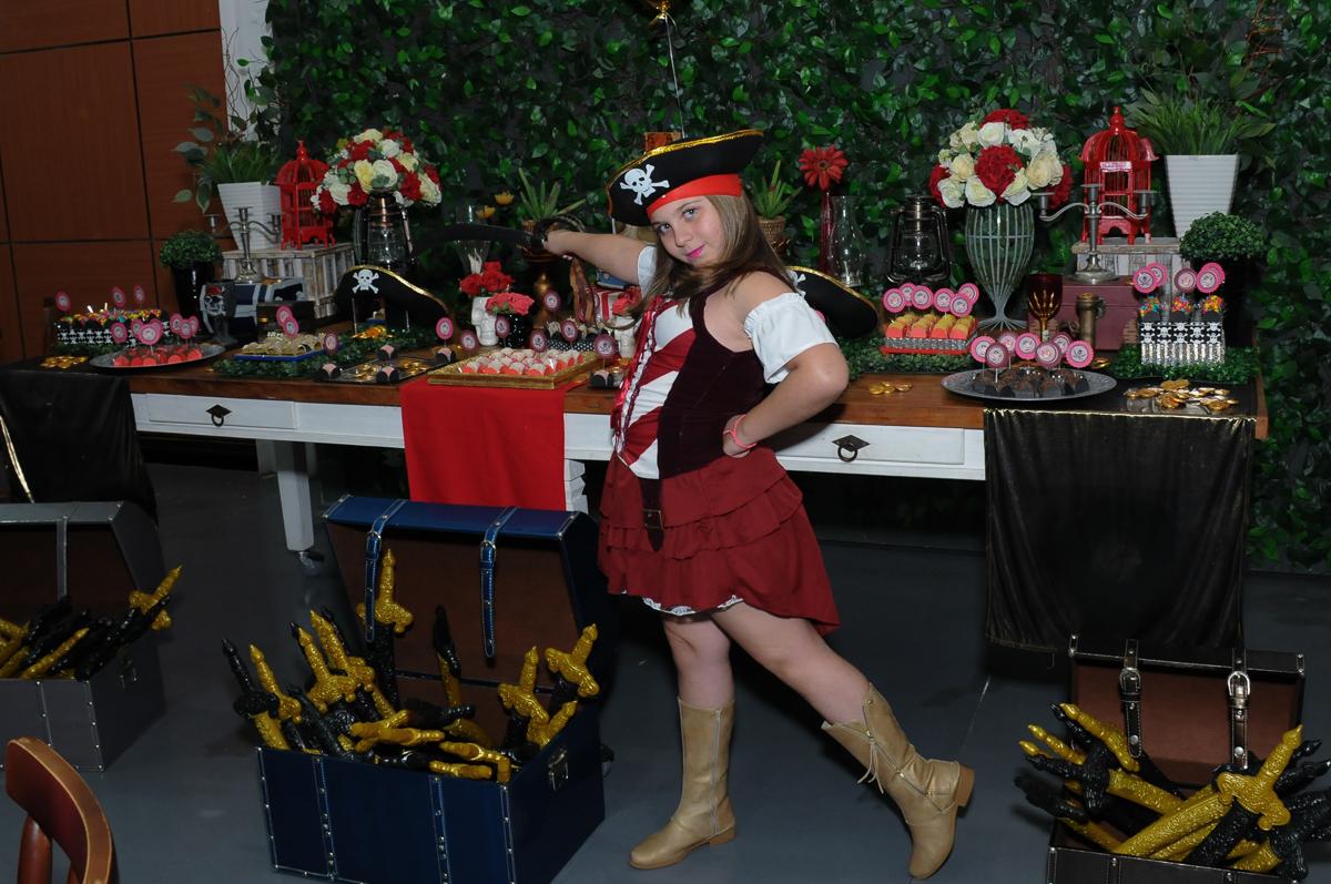 giulia brincando com a espada em frente a mesa piratas do caribe no Buffet Espaço Vila da Arte