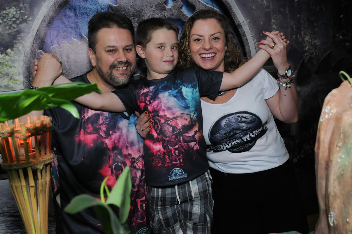 thiago abraçando o papai e a mamãe em frente a mesa decorada dos dinossauros no buffet espaço boo, Lapa, São Paulo
