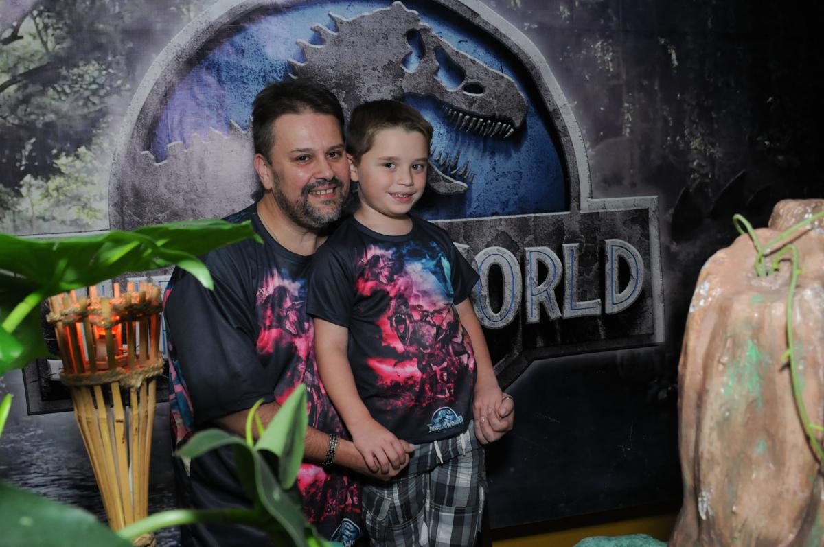 thiago e o papai em frente a mesa decorada dos dinossauros no buffet espaço boo, Lapa, São Paulo