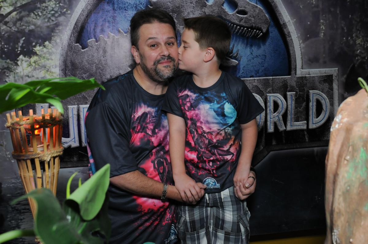 papai ganhando beijinho de thiago em frente a mesa decorada dos dinossauros no buffet espaço boo, Lapa, São Paulo