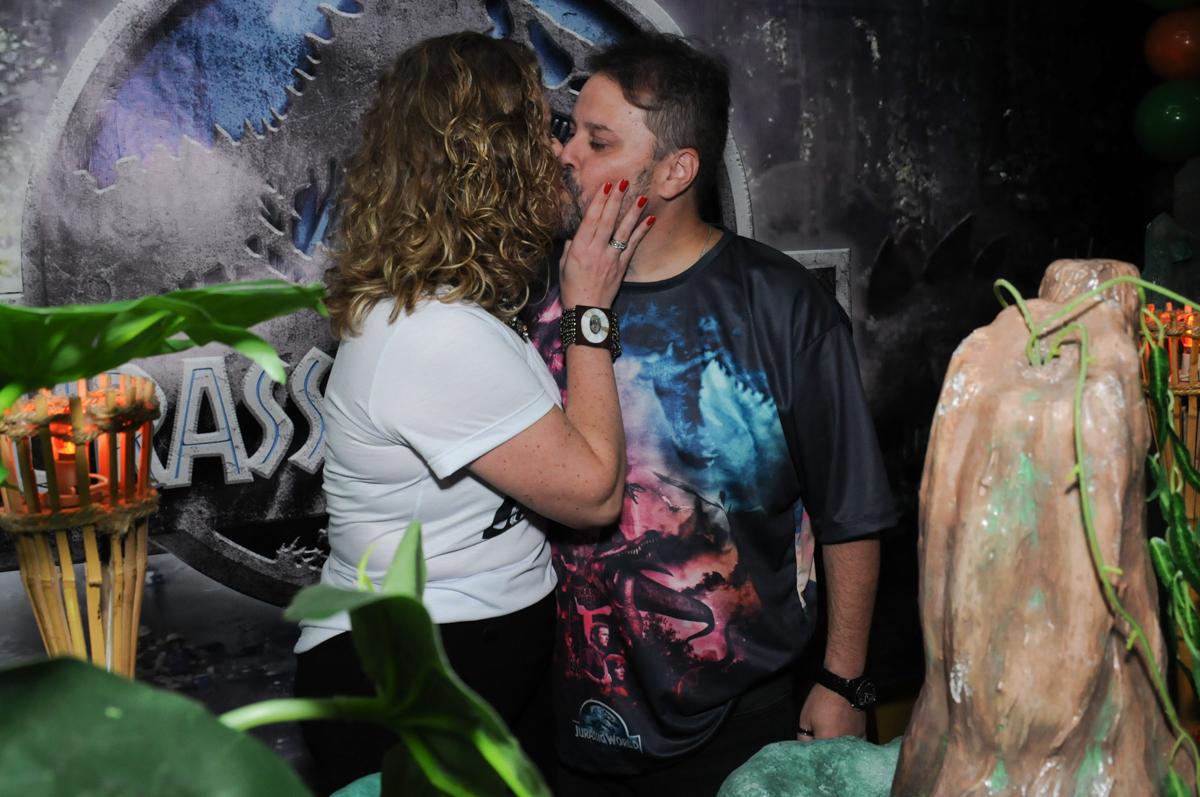 beijinho dos pais em frente a mesa decorada dos dinossauros no buffet espaço boo, Lapa, São Paulo