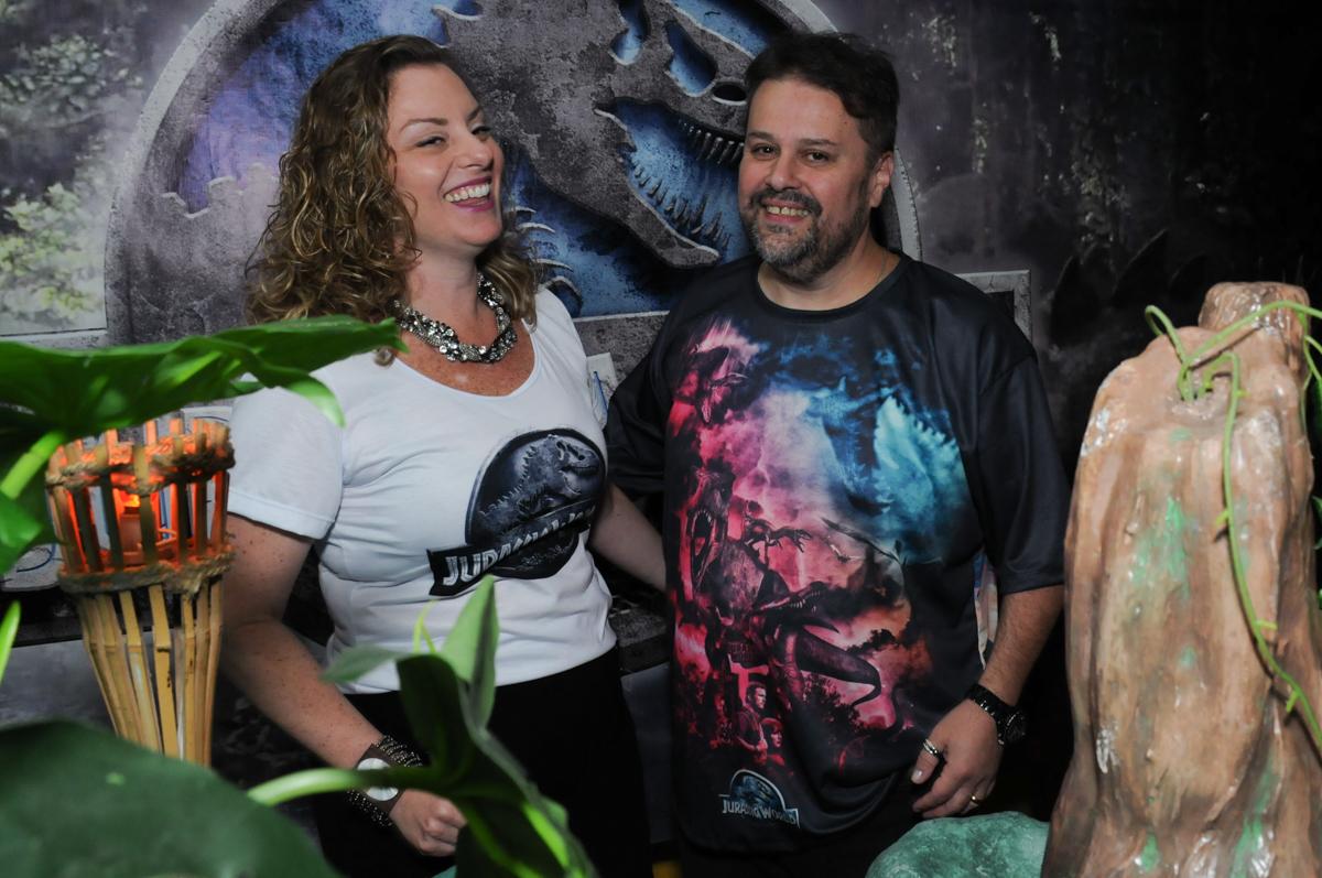 papai e mamãe felizes na festa do thiiago em frente a mesa decorada dos dinossauros no buffet espaço boo, Lapa, São Paulo
