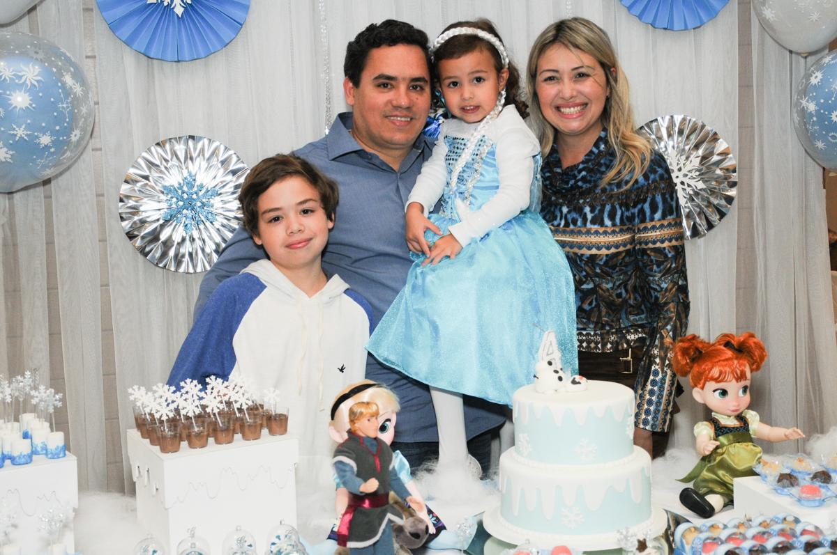 foto da família em frente a mesa frozen no condomínio Granja Vianna