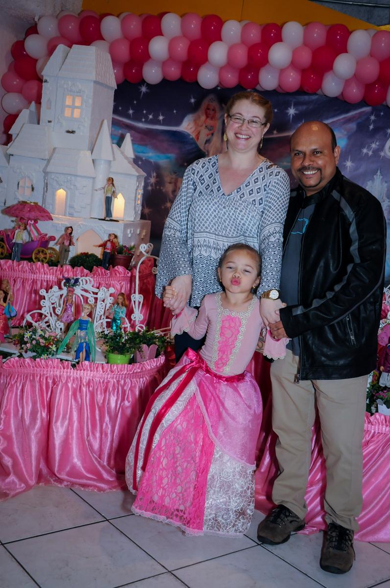 foto da aniversariante dom os pais em frente a mesa decorada barbie no Buffet Fábrica da Alegria, Unidade Osasco