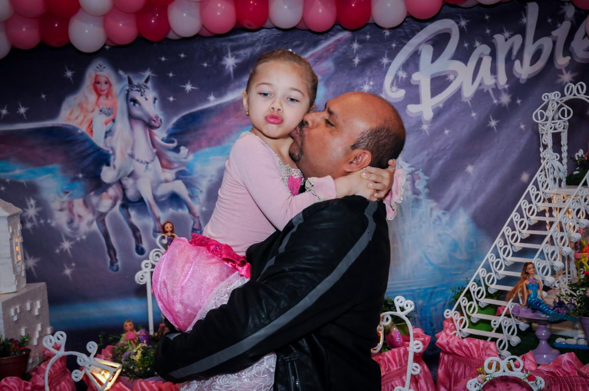 beijo do papai na aniversariante em frente a mesa decorada barbie no Buffet Fábrica da Alegria, Unidade Osasco