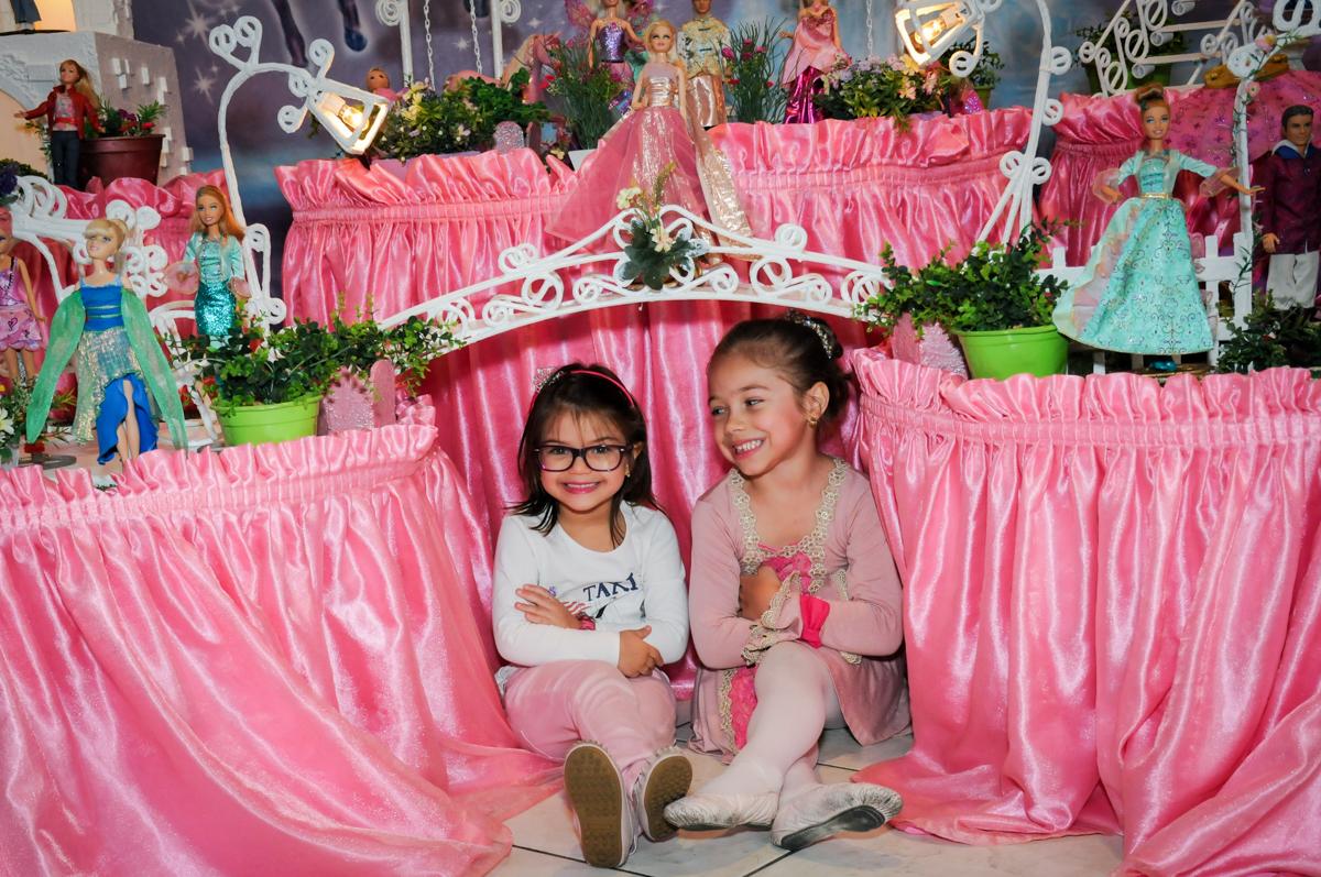 aniversariante e amiguinha em frente a mesa decorada barbie no Buffet Fábrica da Alegria, Unidade Osasco