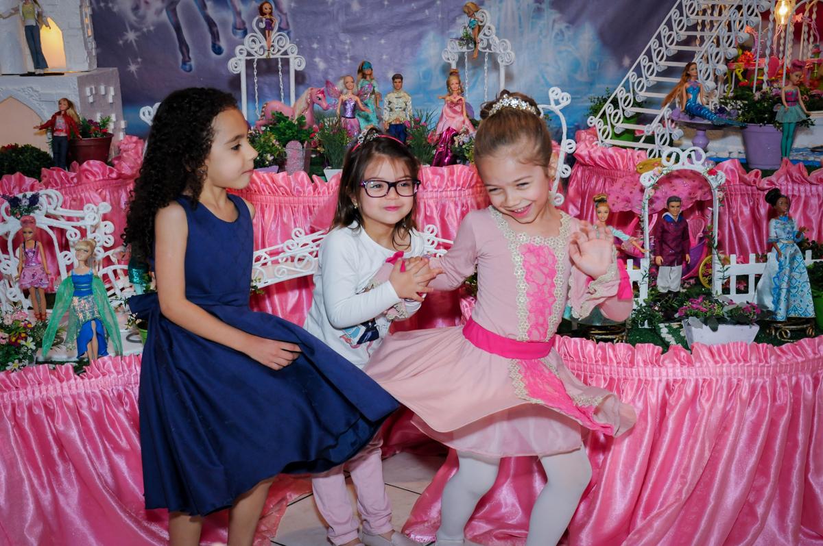 risadas da aniversariante e amigas em frente a mesa decorada barbie no Buffet Fábrica da Alegria, Unidade Osasco